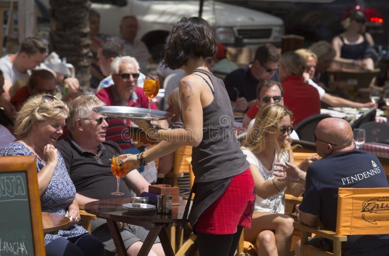 女服务员在旅游大阳台酒吧细节的服务饮料 库存图片