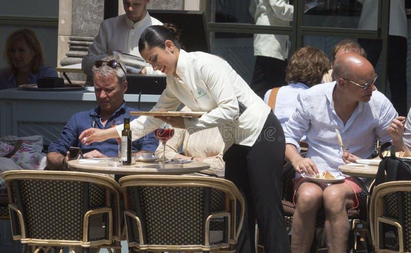 女服务员在旅游晴朗的大阳台酒吧的服务饮料 库存照片