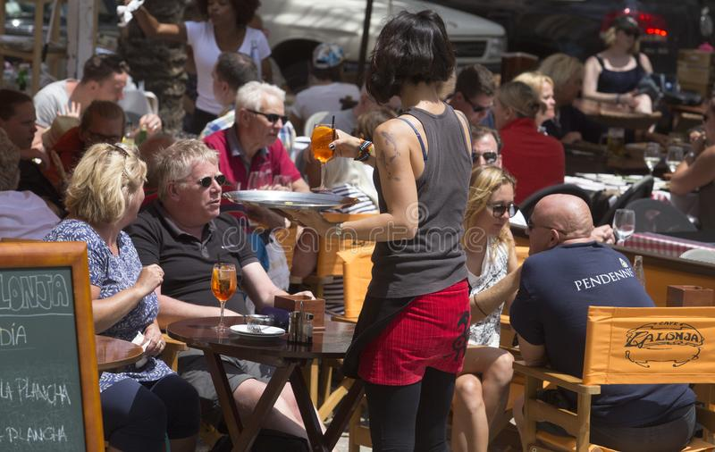女服务员在旅游晴朗的大阳台酒吧的服务饮料 免版税库存照片