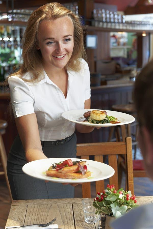 女服务员坐在表上的服务顾客在餐馆 免版税库存照片