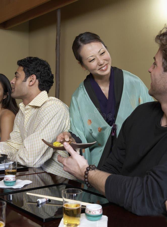 女服务员对顾客的服务寿司在餐馆 免版税库存照片