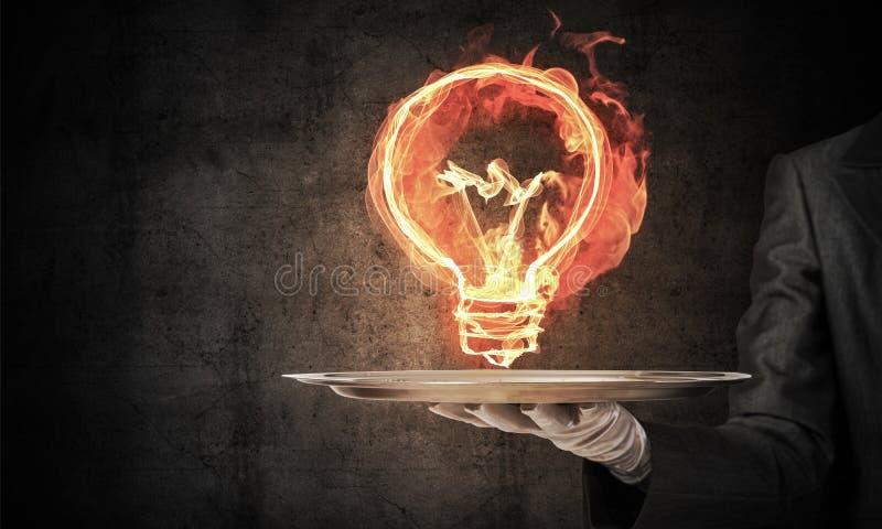 女服务员提出火焰状电灯泡的` s手 库存照片