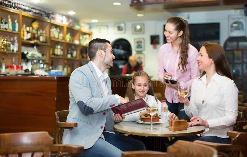 女服务员服务三口之家 免版税库存图片