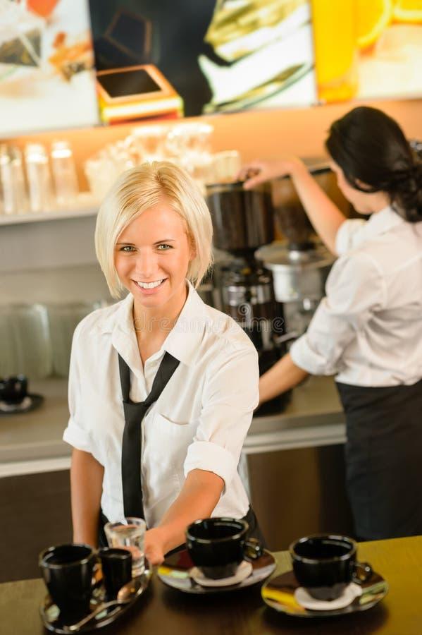 女服务员服务做浓咖啡妇女的咖啡杯 免版税库存图片