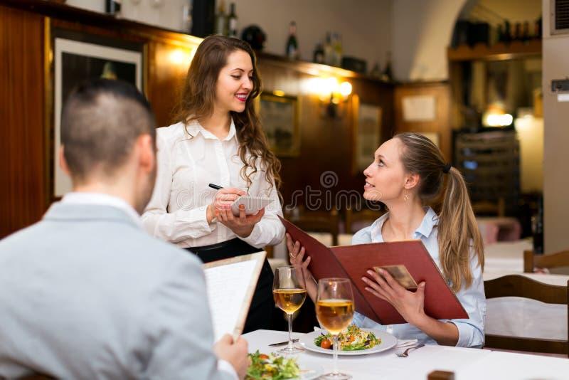 女服务员服务客人在餐馆 图库摄影