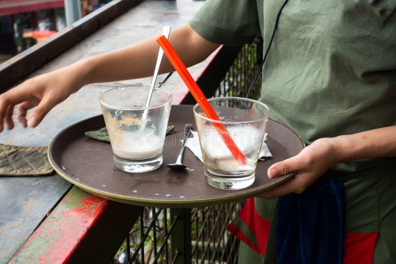 女服务员清洁在咖啡馆的咖啡馆桌 免版税库存图片