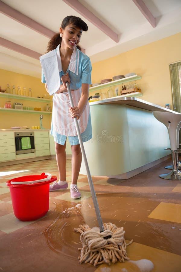 女服务员清洁地板在餐馆 免版税图库摄影