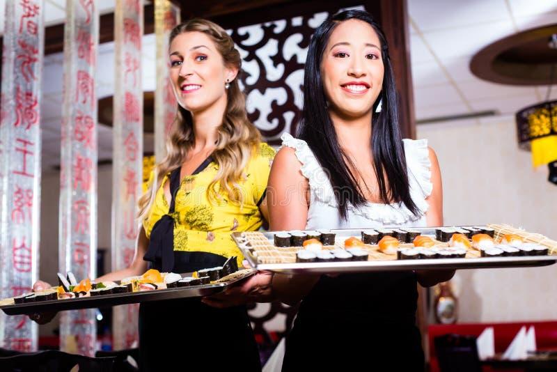 女服务员用寿司在亚洲餐馆 库存图片