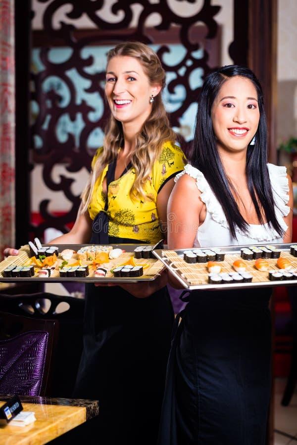 女服务员用寿司在亚洲餐馆 免版税库存图片