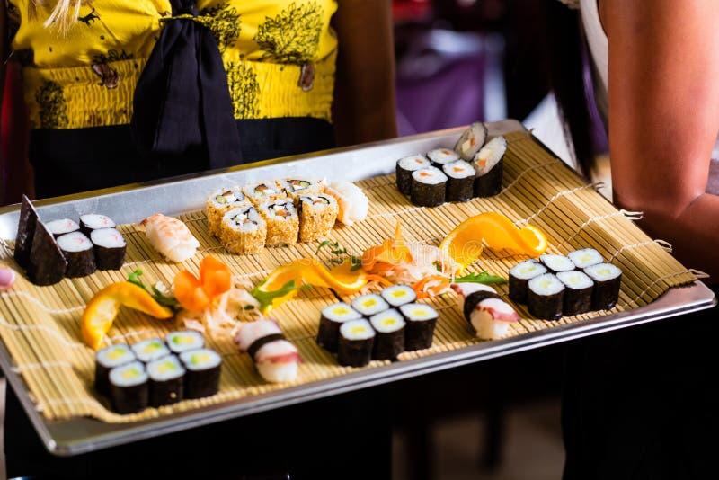 女服务员用寿司在餐馆 免版税库存照片