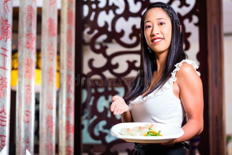 女服务员用寿司在餐馆 免版税图库摄影