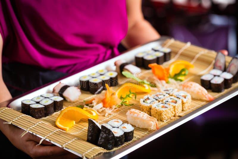 女服务员用寿司在餐馆 免版税库存图片
