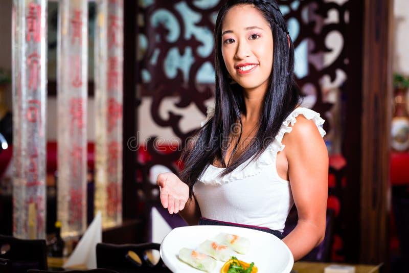 女服务员用寿司在餐馆 库存图片