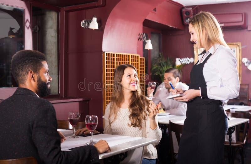 女服务员年轻夫妇的服务膳食在桌上 库存图片