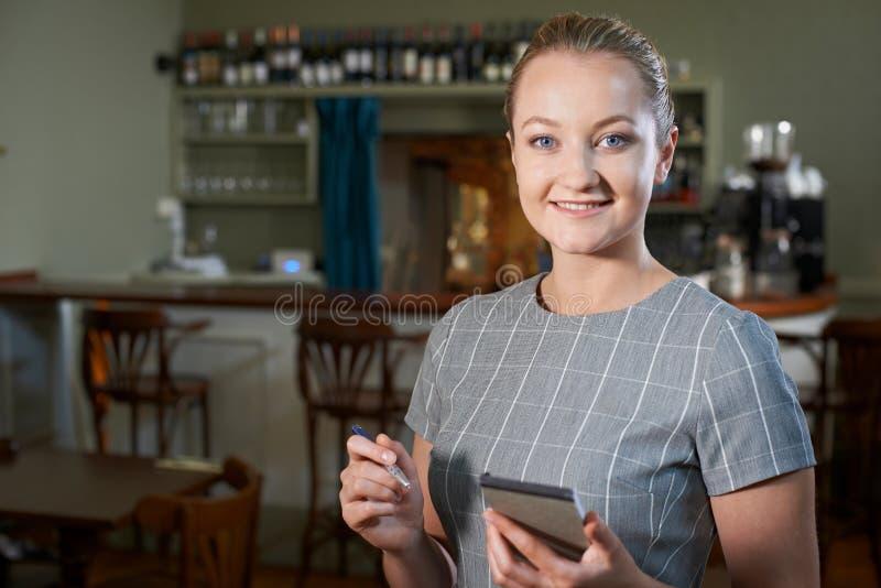 女服务员画象有笔记薄的在餐馆 图库摄影