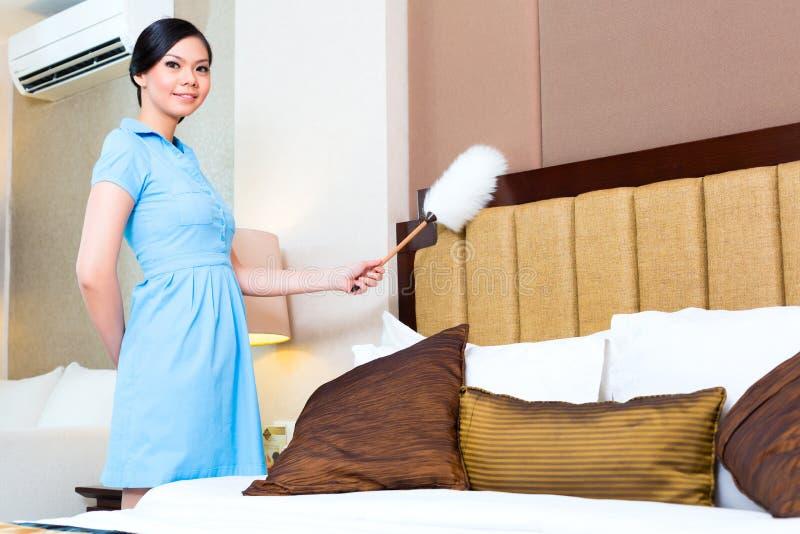 女服务生打扫灰尘在旅馆客房 库存照片