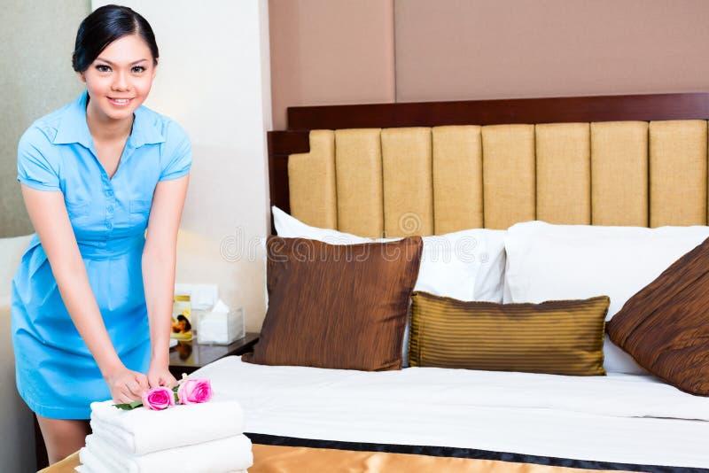 女服务生清洁在亚洲旅馆客房 免版税库存图片