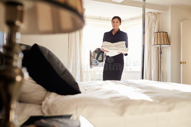 女服务生运载的亚麻布在旅馆卧室,低角度视图 免版税库存照片