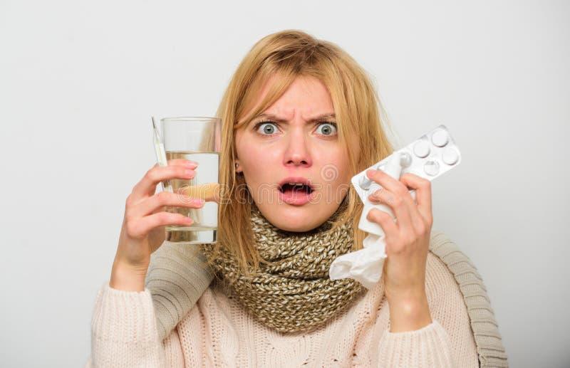 女服温暖的围巾,因为病症或流感 女孩举行玻璃水片剂和温度计轻的背景关闭 免版税库存图片