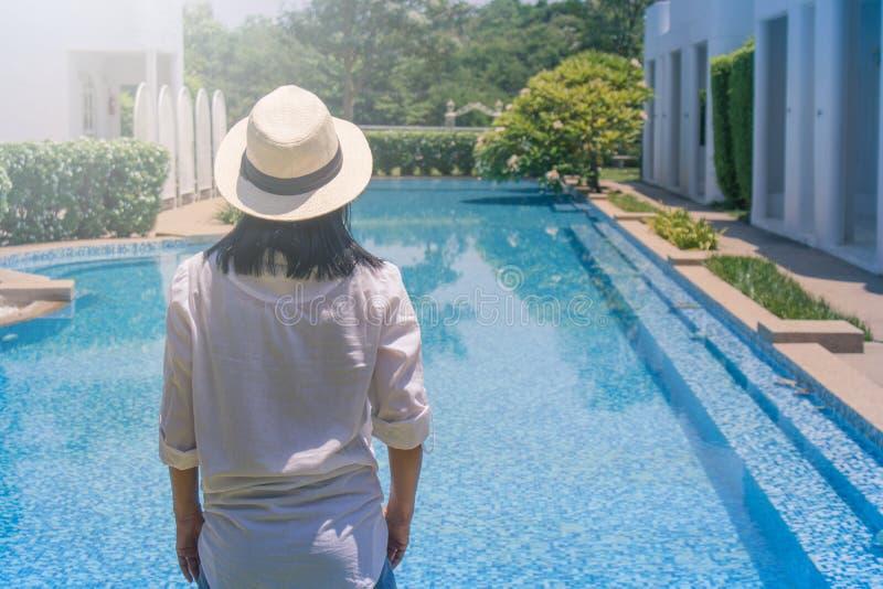 女服白色衬衫和织法帽子,她身分在游泳场边缘放松  免版税图库摄影