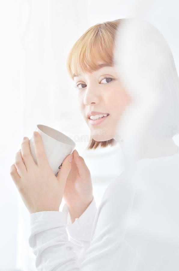 女服白色衬衫 微笑的和饮用的咖啡 图库摄影