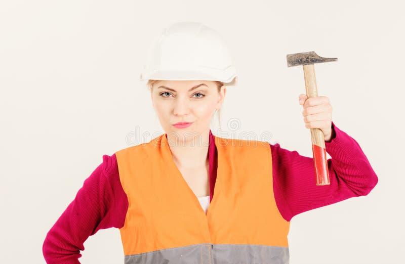 女权主义概念 盔甲或安全帽培养锤子的女孩 免版税库存照片