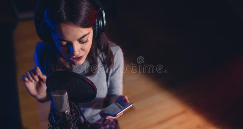 女歌手唱歌歌曲在录音室 免版税库存照片