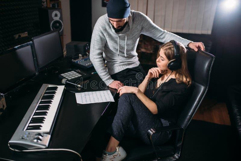 女歌手在音乐演播室听歌曲纪录 免版税库存图片