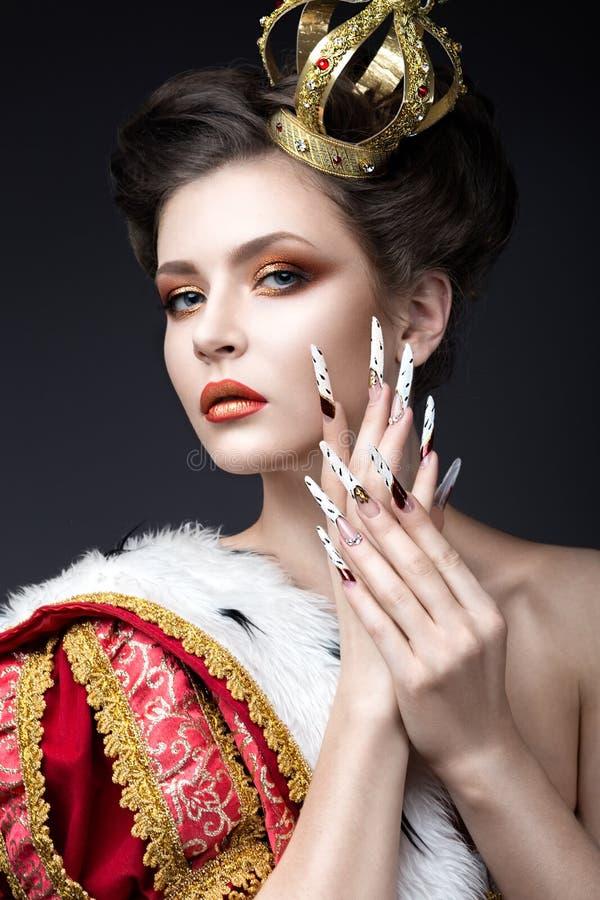 女王/王后的图象的美丽的女孩披风的与在头和长的钉子的一个冠 秀丽表面 免版税图库摄影