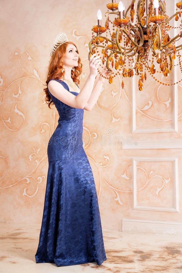 女王/王后,有冠的皇家人在蓝色礼服 枝形吊灯 免版税库存图片