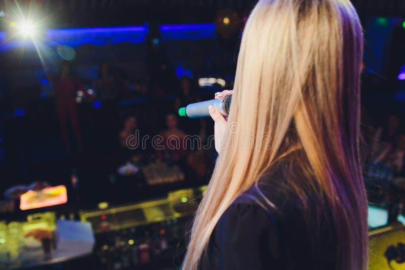 女生拿着在左手的黑无线话筒和做演说与弄脏 免版税图库摄影