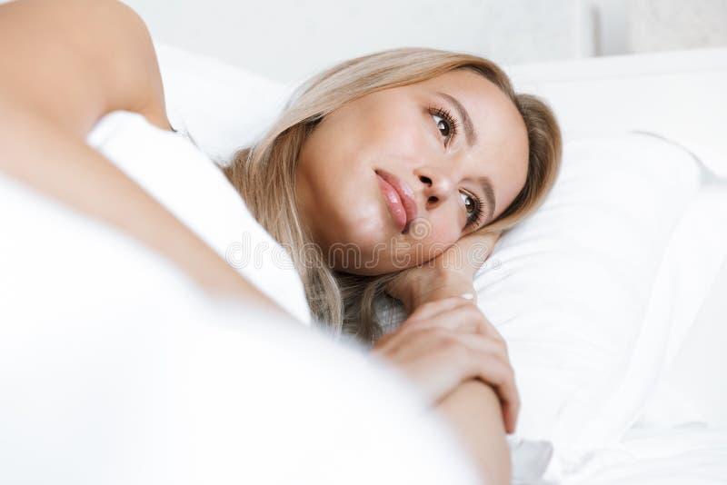 女用贴身内衣裤内衣谎言的年轻女人在床上在家 库存图片