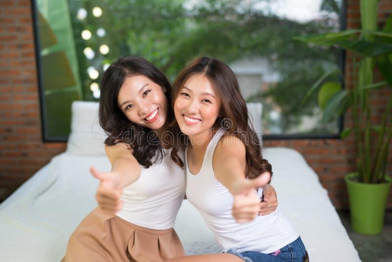 女用贴身内衣裤的两个女性朋友在床上 免版税库存图片