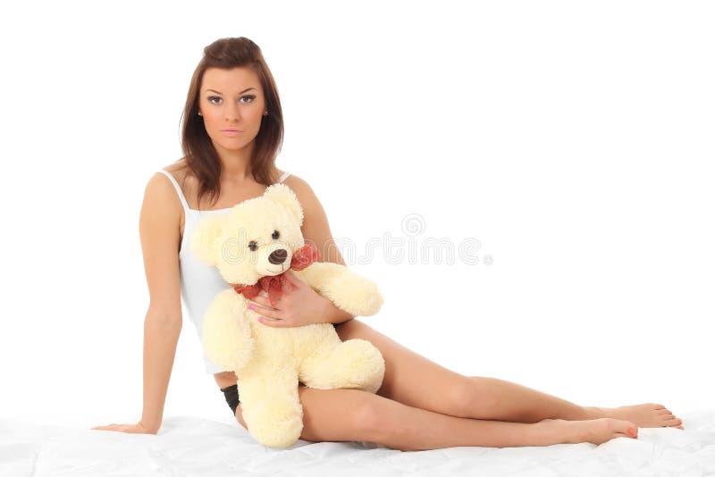 女用贴身内衣裤的女孩有玩具熊的 免版税库存照片