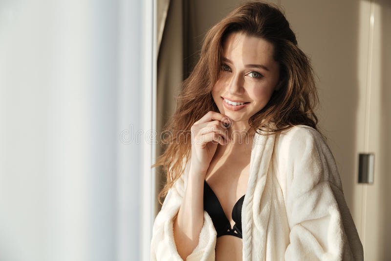 女用贴身内衣裤和浴巾的愉快的肉欲的少妇在家 库存图片