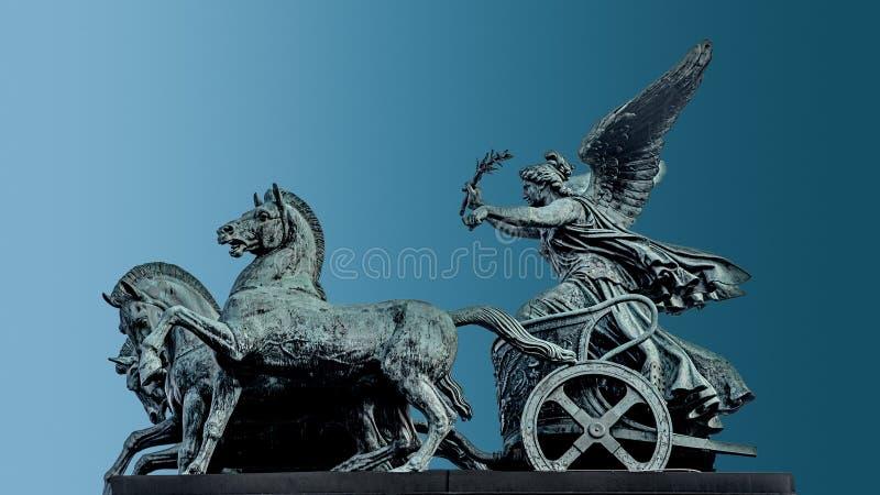 女神胜利,耐克古铜色四马二轮战车雕象,在奥地利议会屋顶在维也纳,奥地利,被隔绝在蓝色背景, 库存照片