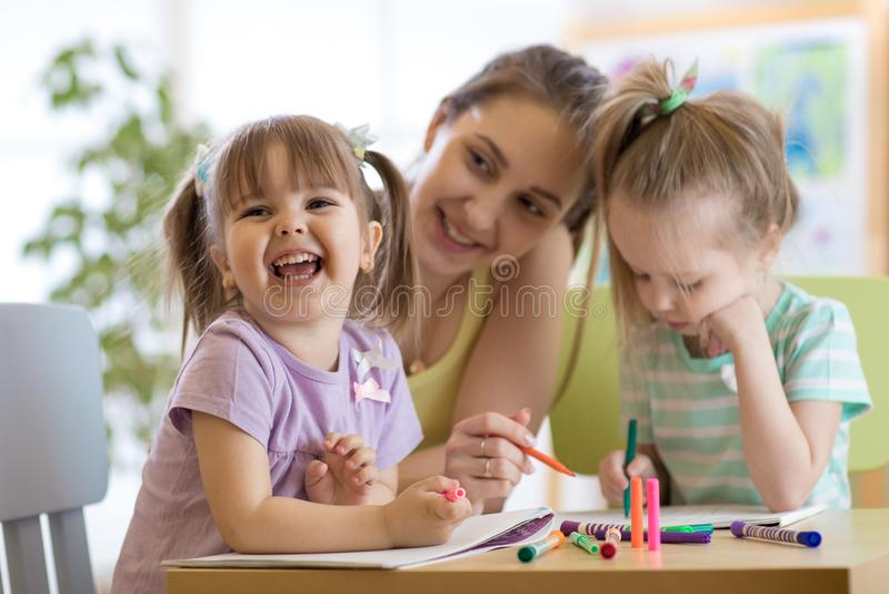 女老师与孩子一起使用在学龄前教室 免版税库存图片