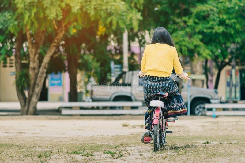 女老师乘驾后面看法骑自行车教学生 库存图片