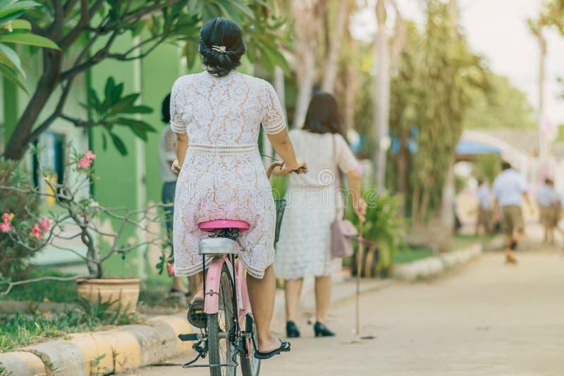 女老师乘驾后面看法骑自行车教学生 库存照片