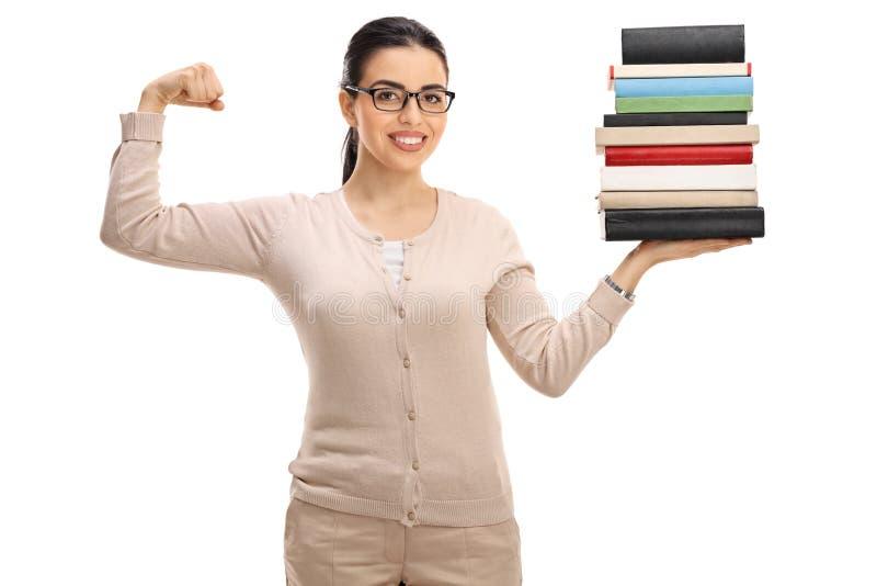 年轻女老师藏品堆书和屈曲二头肌 免版税图库摄影