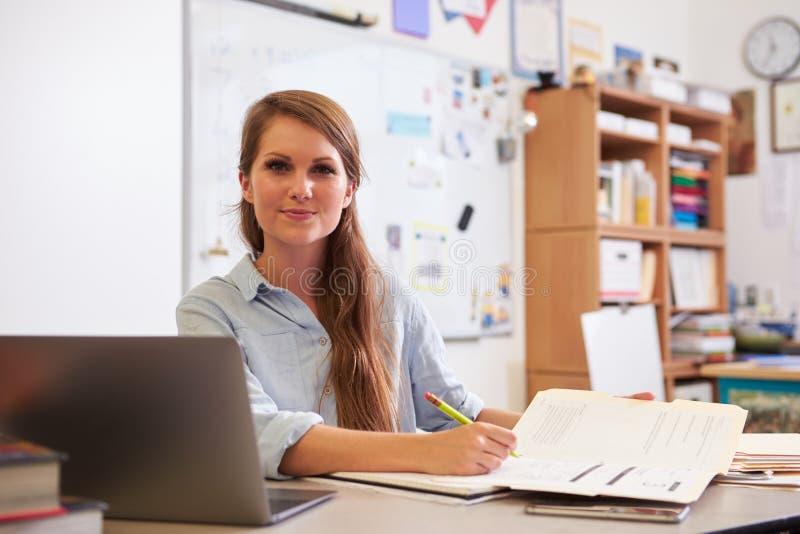 年轻女老师画象看对照相机的书桌的 免版税库存图片