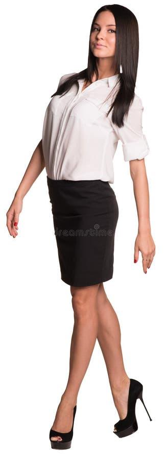 女衬衫和裙子步行的美丽的女实业家 图库摄影