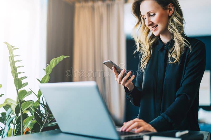 女衬衫的年轻微笑的女实业家站立室内,研究计算机,当使用智能手机时 女孩在家工作 免版税库存图片