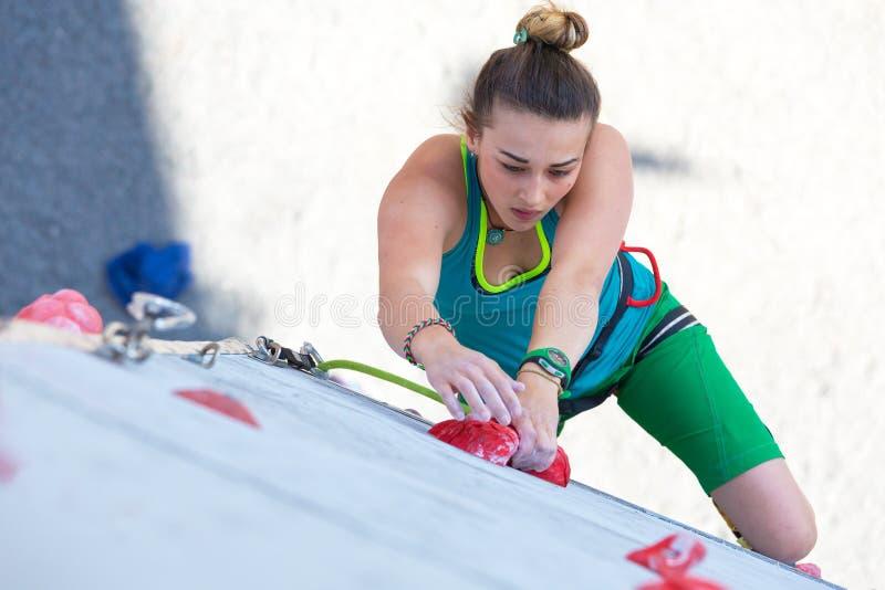 女运动员在上升的墙壁采取坚硬行动 免版税库存图片