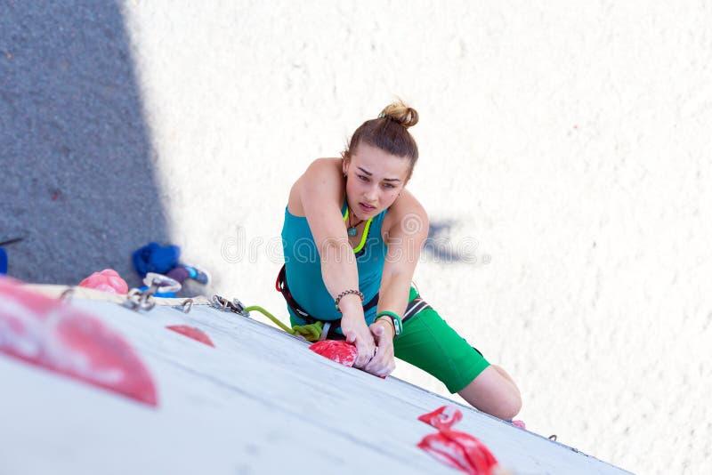 女运动员在上升的墙壁采取坚硬行动 库存图片
