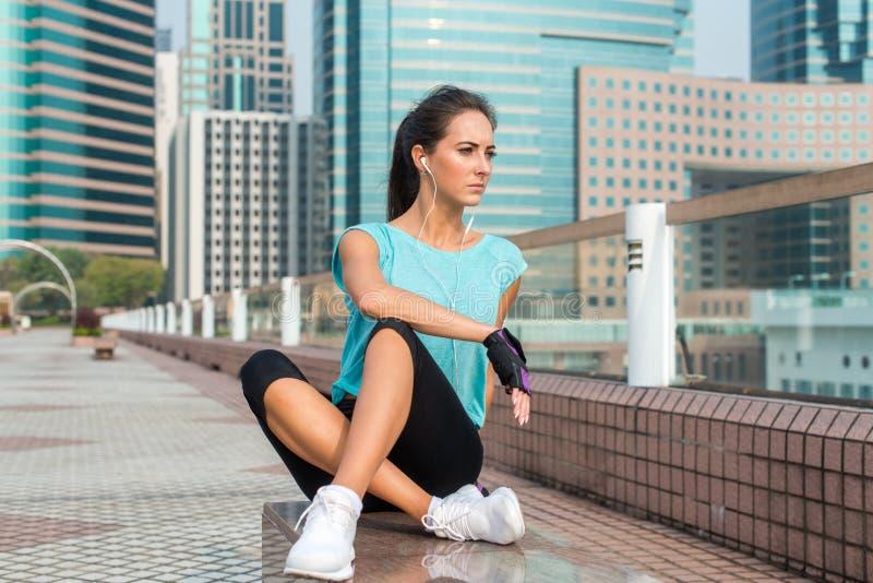 女运动员在跑的或训练基于疲倦了长凳以后 放松和听到音乐的适合的少妇 免版税库存图片