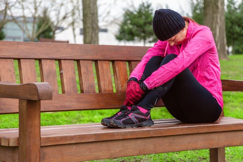 女运动员在都市公园的训练轨道的一个冷的冬日疲倦了或压下了基于一条长凳 免版税库存图片