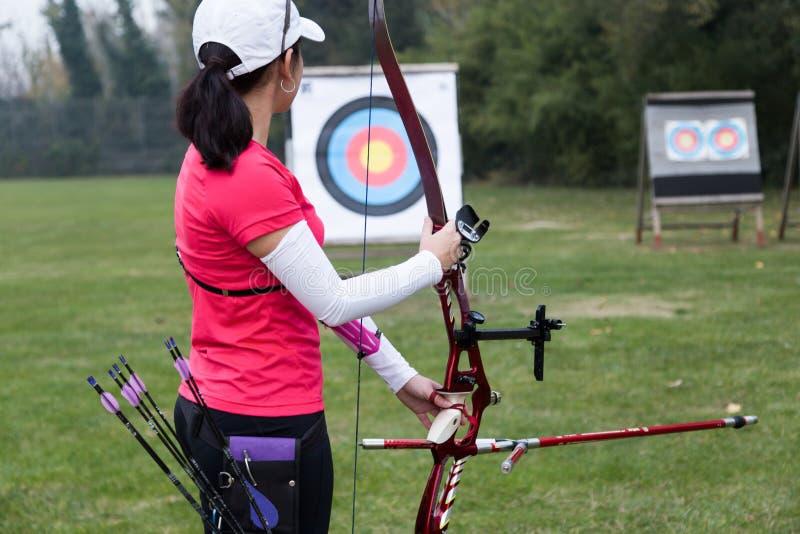 女运动员实践的射箭在体育场内 免版税库存照片