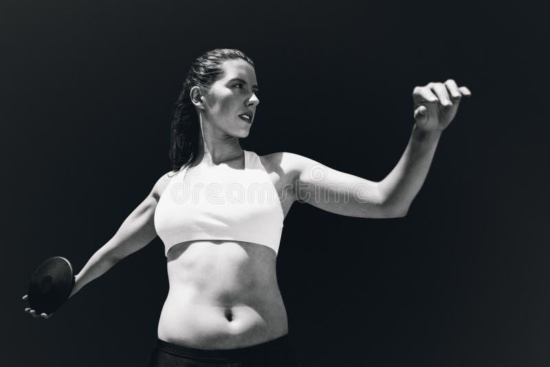 女运动员实践的掷铁饼正面图的综合图象  免版税库存图片