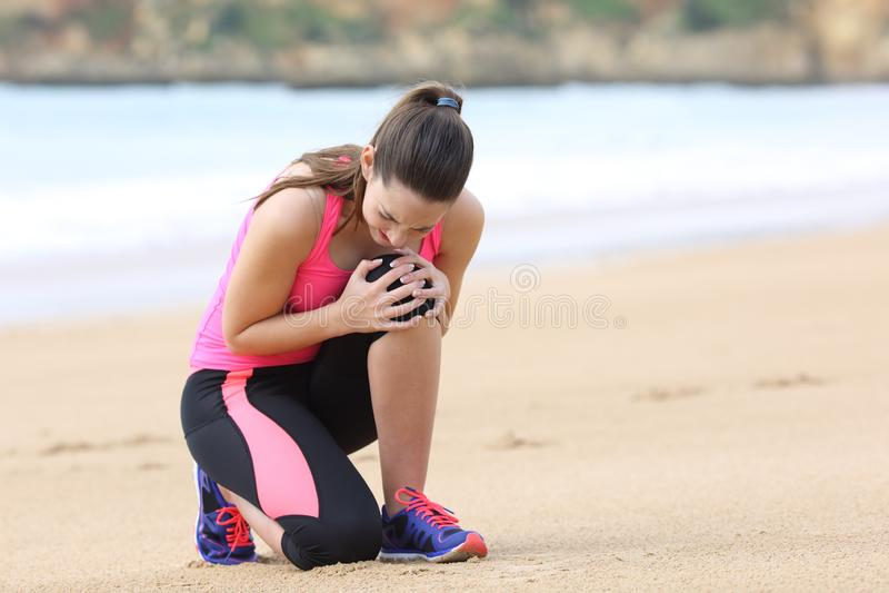 女运动员痛苦膝盖疼痛在赛跑以后 免版税图库摄影